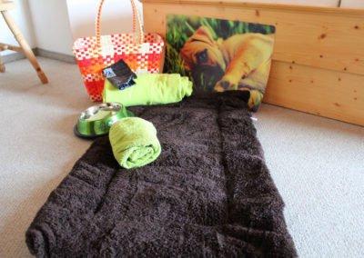 Korb mit Hundedecke, Hundeschlafplatz, Hundenapf, Portionslöffel fürs Hundefutter und einem Hundehandtuch